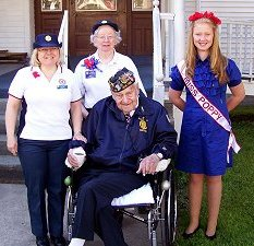 J Petersen and S Witchella of Auxiliary, and Miss Poppy stand beside vet Bud Mohr.